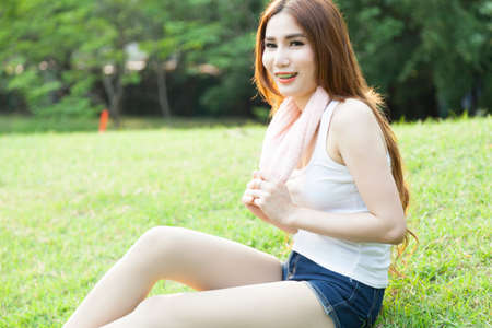 Woman sitting on the grass. After jogging in the park. photo