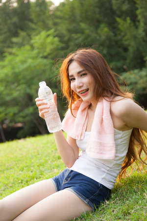 Woman sitting rest after exercise. Hand holding a bottle of water and sit On the lawn. photo