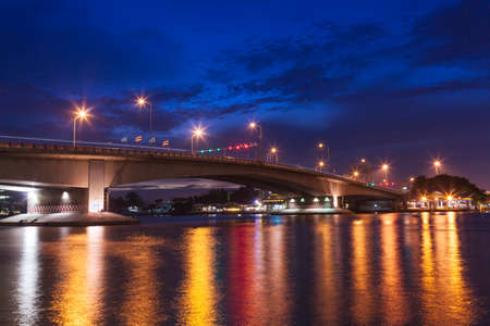bridge over river in the evening. The light from the lamp to the reflector surface. photo