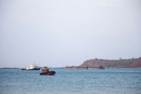 compared: Large cargo ship Boats moored in the sea to make sense compared to the coast. Editorial