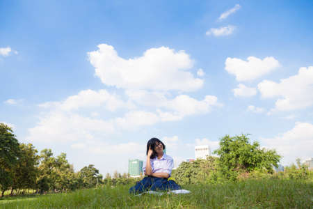 Student homework sitting on the lawn. In the Park on a clear day. The sky is clearing up. photo