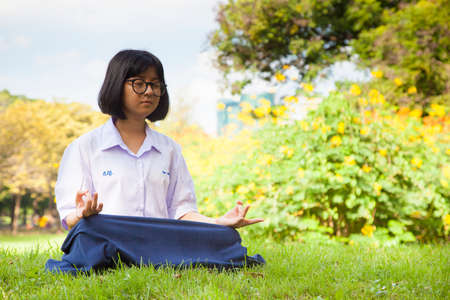 Schoolgirl are meditating. The grass in the park. Weather cloudy and clear sky. photo