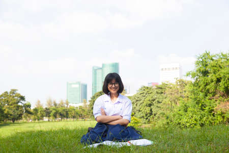 Girl sitting and smiling. On the lawn a happy and relaxation. On a clear sunny sky. photo