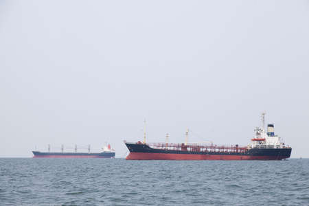 Large cargo ship Boats moored in the sea to make sense compared to the coast. photo