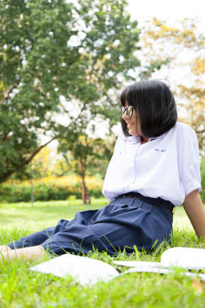 Schoolgirl is sitting and relaxing. On the grass in the park. While being homework photo