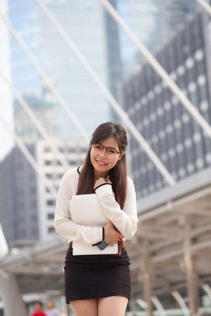 Happy asian businesswoman hold paper and document file.smile and stand on sidewalk. photo