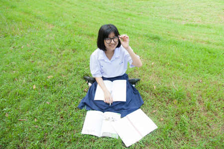 Schoolgirl was reading on the lawn. Smiling and happy within the park. photo