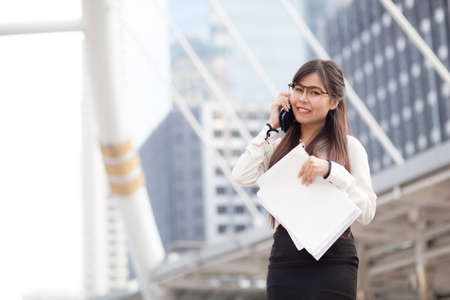 Asian business woman talking smart phone.smile and standing on sidewalk.holding paper and document file. photo