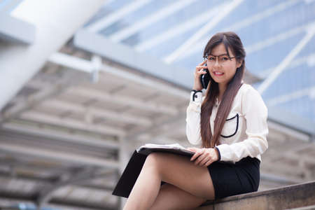 sidewalk talk: Businesswoman talking phone. Happy while talking on the phone. Stock Photo