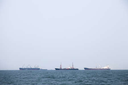 compared: Large cargo ship Boats moored in the sea to make sense compared to the coast. Stock Photo
