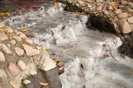 well water: water flowing from the well. Water flowing from the hot springs. Stock Photo