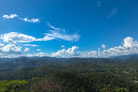 luxuriant: Forested mountains and sky. Luxuriant trees of the forest-covered mountains. The sky is clearing up.