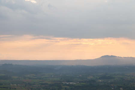 agricultural area: Mountains and forests in the evening. Nearby sun darkens. An agricultural area near the mountains.