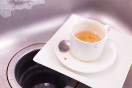 Coffee cup and white plates. Lay piled in the sink in the kitchen.... photo