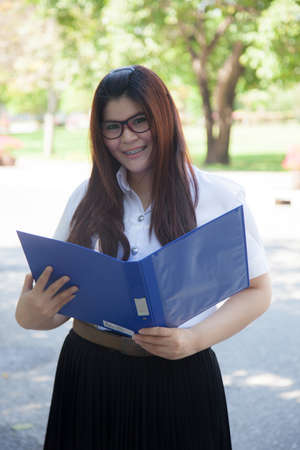 exists: Student holding a blue documents. Student wearing glasses, standing smiling and holding a file exists.