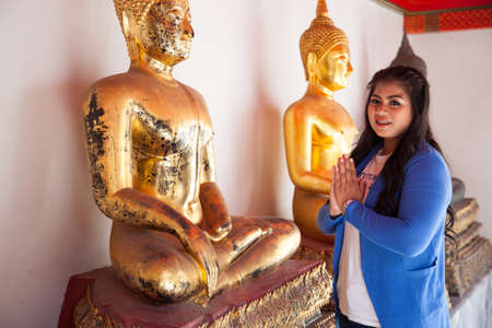 Woman worshiping Buddha in temple. Buddha in a temple tourism in Thailand. Stock Photo