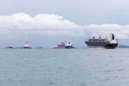 await: Cargo ship. Parking in the sea to await transportation to the port.