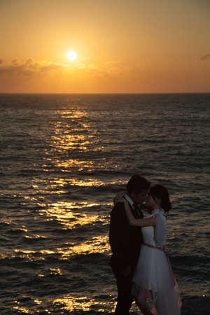 darken: Couple standing by the sea. Romantic sun sets. The sky began to darken