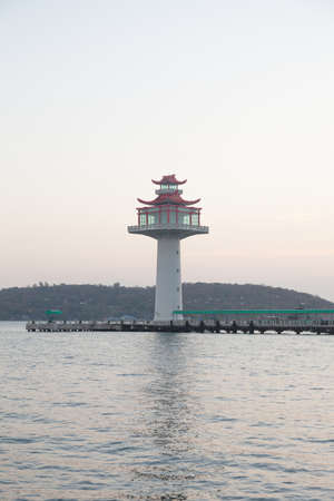 compared: Lighthouse tower. Pier compared coast of the island. In the morning