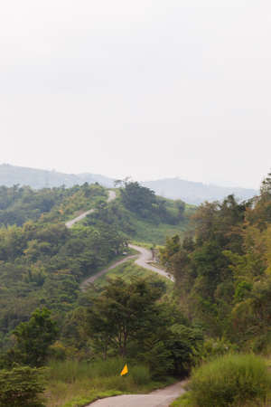 both sides: Curvy roads on the mountain. Turn on the mountain road with trees on both sides. Stock Photo