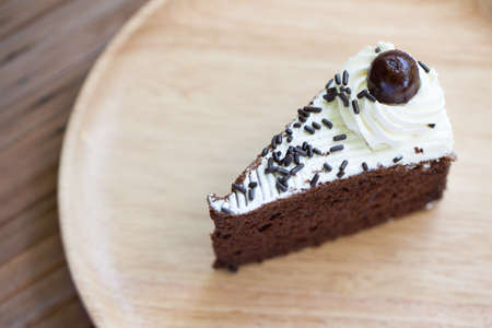 well made: Chocolate cake, put it on a plate placed on a wooden table made from wood as well.