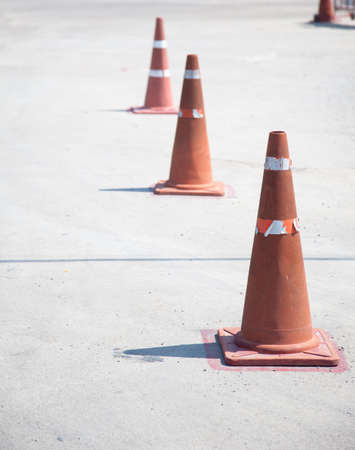traffic cones: Putting together a line of traffic cones on the road to car traffic.