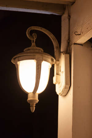 sconce: lantern on the wooden front porch. Open to light at night