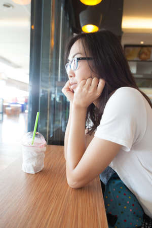 think through: Asia woman looking out window. and ice tea on table in cafe.