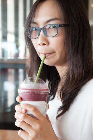 joy and happy asia woman drinking ice tea.portrait woman wear eyeglasses.