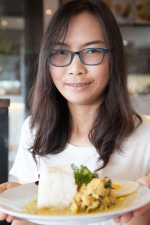 asia woman hold thai food.woman wear eyeglasses. relax and smile wear eyeglasses.