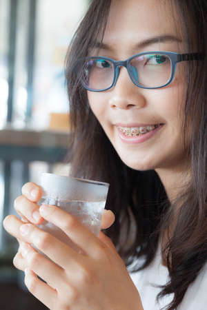dring: Asia woman drink water.smile woman dring water.woman wear eyeglasses smile and relax.