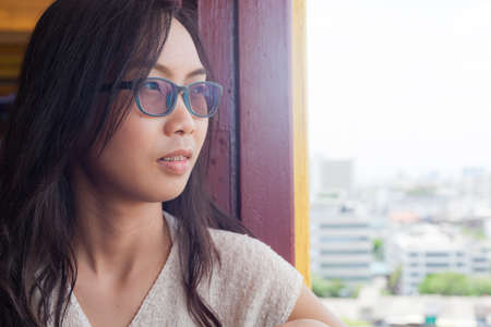 look out: asia woman look out window.woman wear eyeglasses.