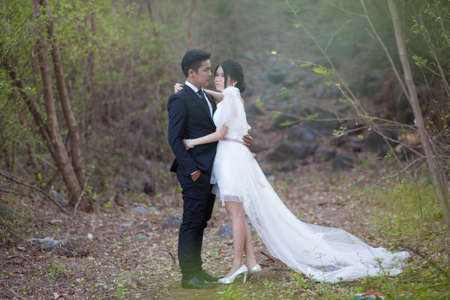 prewedding: Bride and groom. Standing in the forest with the trees surrounding the side. Stock Photo