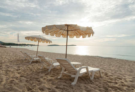 romance sky: Beds and umbrellas lined up on the beach by the sea. Sleeping in tourism
