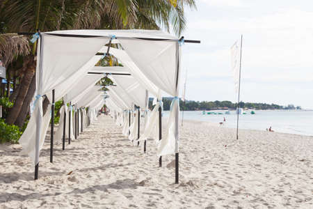 White tent on the beach Coconut trees by the sea In the morning for the wedding ceremony.