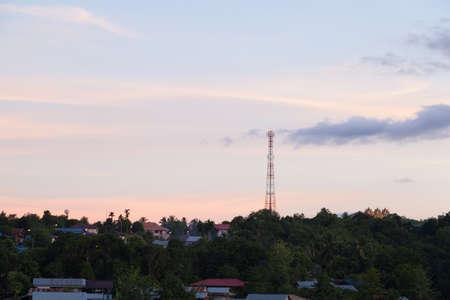 darken: Telecommunications antenna Set in a village in the jungle. In the evening, the sun began to darken.