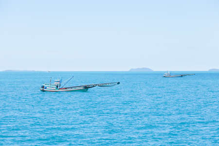 sea water: Small fishing boat That sailed on the sea during a fishing during the daytime.