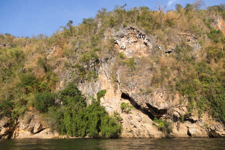 adjacent: Cliffs adjacent river. High cliffs adjacent to the river. There are more trees on a small cliff.
