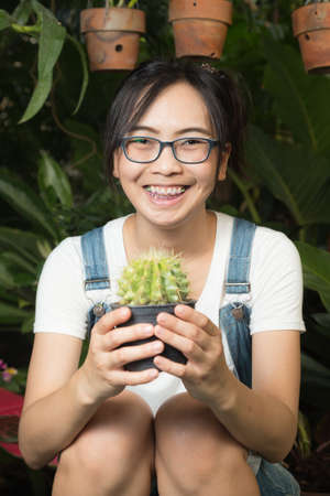 greenhouse and ecology: woman, cactus, plant, background, gardening, pot, beautiful, beauty, green, care, female, holding, girl, colorful, flower, ecology, garden, white, nature, greenhouse, people, person, happy, summer, decoration, lady, hobby, spring, leaf, lifestyle Stock Photo