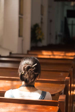 One woman sitting in church. The sun shines through the window to the left of the church.