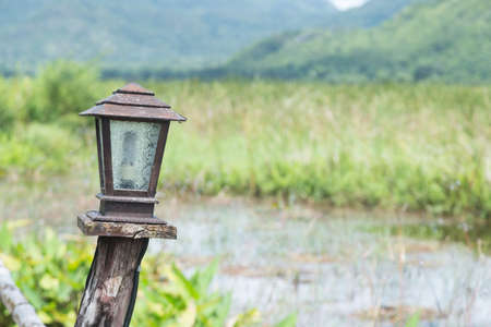 Lamp made of wood decorations on the path next to the river. Stock Photo