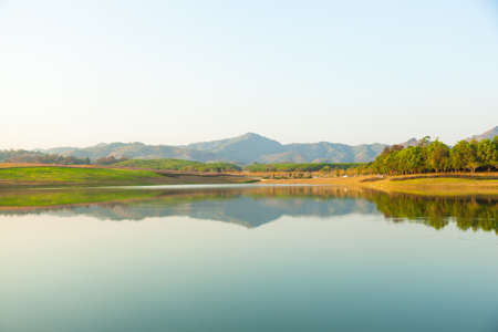 Reflection on river of hills in riverside in midday