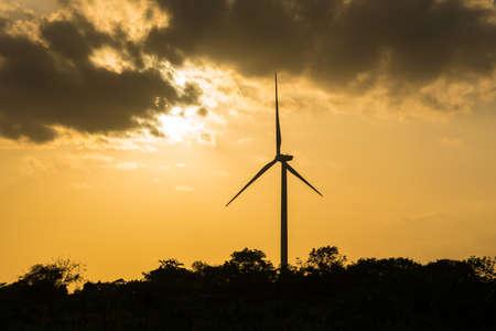 Wind turbine power. Large wind turbine generates electricity. In the sunset