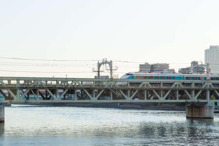 train on the bridge is crossing the river. In Tokyo city at daytime.