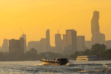Boat traffic river in evening. Bangkok city and building skyscraper background in sunset.