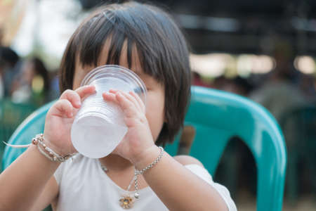 Child girl asian girl drinking water in glass plastic. hold and drink water in glass plastic.