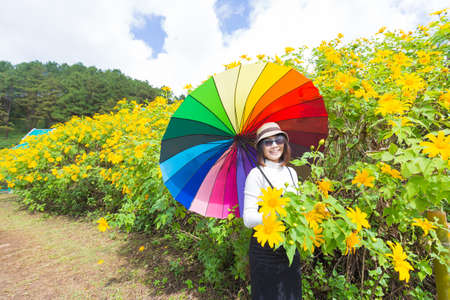 Asian woman hold multicolor umbrella. Relax and happy holiday travel in flower field.