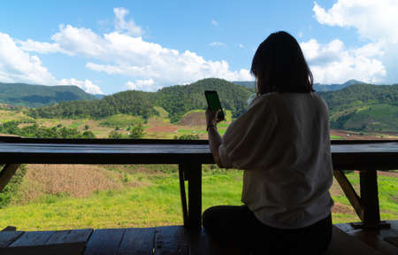 Silhouette woman using smart phone. Background mountain and forest in summer season. Фото со стока
