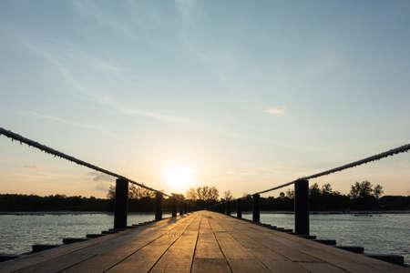 Wooden bridge sea in sunset. Sunlight and sun in evening. Imagens