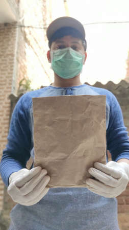 Courier Boy in Protective mask and medical gloves delivers paper Bag, Delivery under quarantine, disease outbreak, corona virus covid-19 pandemic conditions.